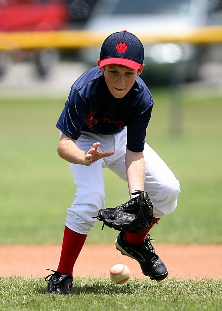 Is softball safe for children? Child demonstrating correct fielding position for ground balls