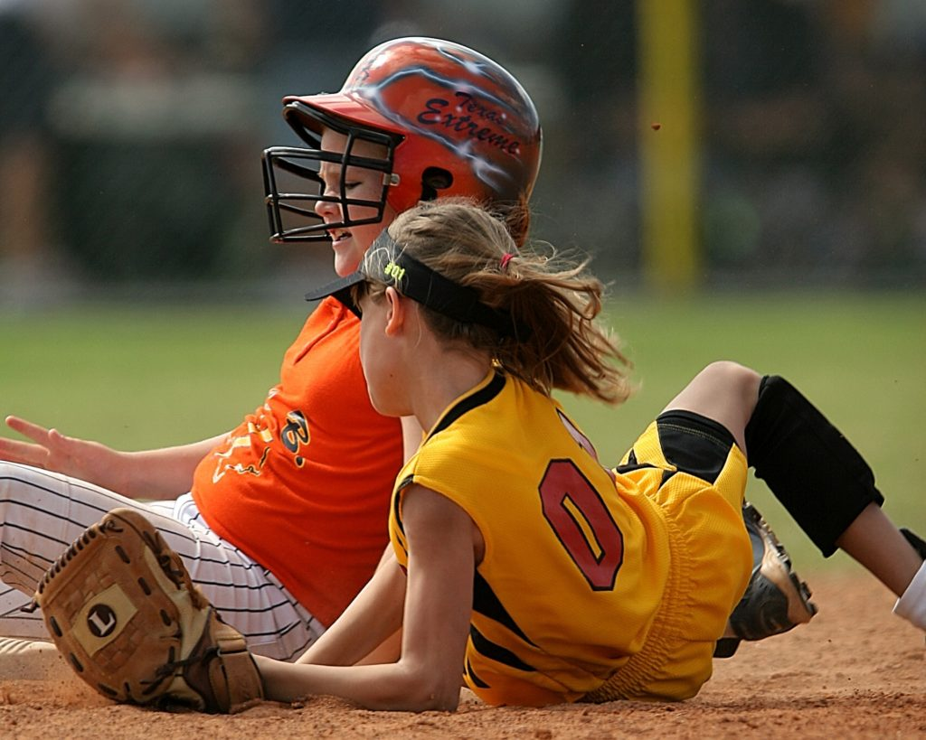 Is softball safe for children? Two children playing softball, collision on the plate.